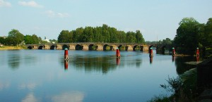 Bild på Stenbron i Karlstad. Blått vatten, blå himmel och en gammal Stenbro. Tagen sommartid.